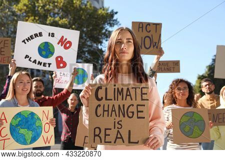 Group Of People With Posters Protesting Against Climate Change On City Street