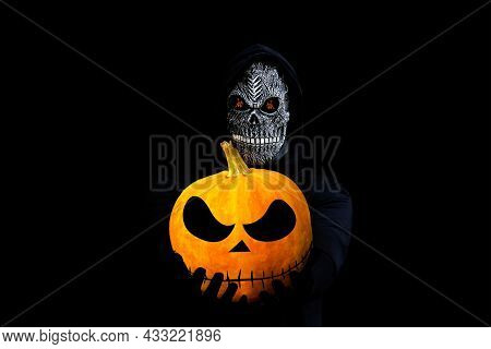 Isolated Grim Reaper Holding Halloween Pumpkin Head. Man In Death Mask With Fire Flame In Eyes And G
