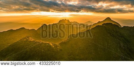 Panoramic Beautiful Mountain Peaks Topped With Sky, Cloud And Blast Horizon Sun, And Decorated With