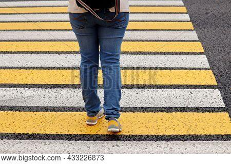 Woman In Jeans Crossing The Street, Female Legs In Sneakers On Pedestrian Crossing. Concept Of Road