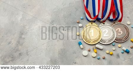 Doping For Athletes. Gold, Silver And Bronze Medal And Pills With Capsules On A Gray Background