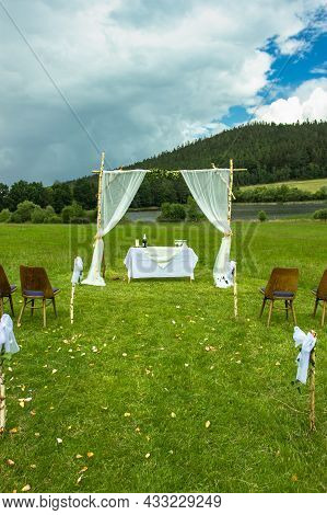 Boho Wedding Decoration. Wedding On Spring Meadow.natural Wedding Arch Decorated With Cloth And Flow