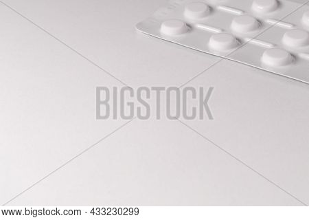 White Pack Of Tablets On A White Background. A Packet Of Tablets Is Placed In The Corner Of The Phot