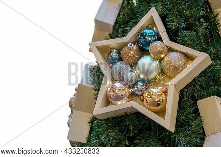 Fragment Of A Christmas Tree Decorated With Decorative Wooden Elements In The Shape Of A Star. Chris