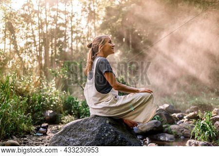 Portrait Of A Relaxed Woman Sitting In A Rock In The Rainforest While The Sun Rays Illuminating Her