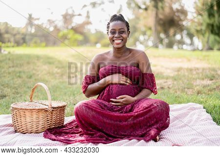 African Woman Caressing Her Pregnant Belly While Doing A Picnic In Park - Maternity Lifestyle Concep