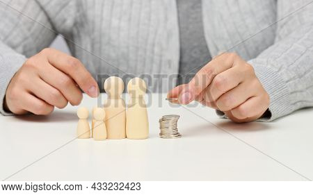 Female Hand Puts Coins In A Pile And Wooden Figurines Of A Family On A White Table. Economy And Inve