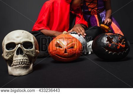 Cropped View Of African American Siblings In Halloween Costumes Holding Carved Pumpkins On Black