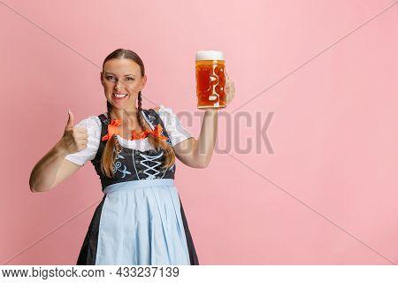 Adorable Oktoberfest Woman, Waitress Wearing A Traditional Bavarian Or German Dirndl Holding One Lit