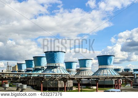 Rows Of Water Fan Cooling Towers For Cooling Circulating Water Of Chemical Plant Under Cloudy Blue S