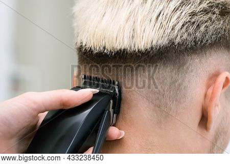 Haircut Process Of Blond Young Man With Hair Clipper In Armchair In Barbershop Salon, Barbershop Con