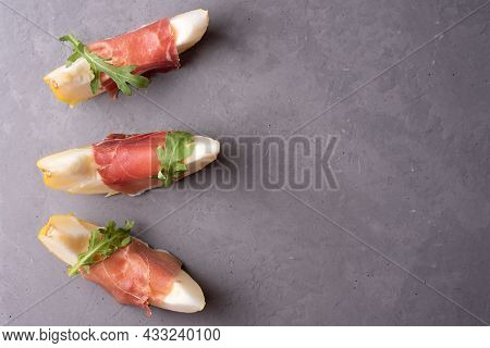 Fresh Melon Wedges With Prosciutto And Arugula On Gray Concrete Background, Italian Ham And Fruit Ap