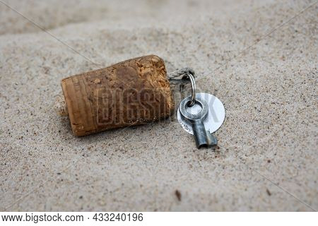 A Key For A Lock, Padlock With A Cork Tag Lies In The Sand.