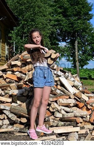 Beautiful Girl With Long Hair In White T-shirt And Denim Shorts Puts Firewood In Pile. Concept Of Ha