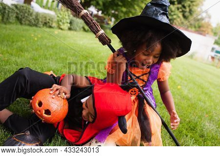 African American Siblings In Halloween Costumes Screaming While Playing On Backyard