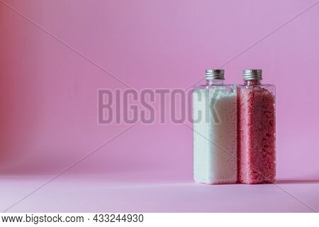 Bath Shimmer And Bath Beads Stand In Transparent Bottles On A Pink Background With Empty Space. High