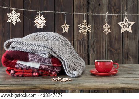 Stack Of Plaids, Cup Of Tea  And Christmas Decorations On Old Wooden Background