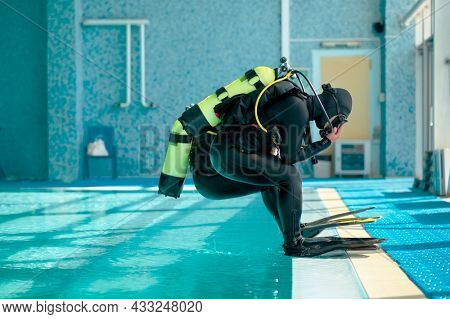 Male divers in scuba gear jump into the pool
