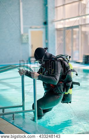 Male diver in scuba gear climb out of the pool