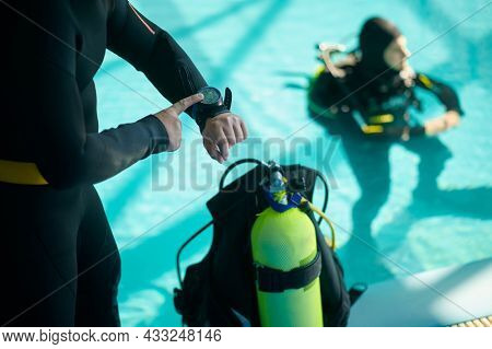 Diver and divemaster mark the dive time, diving