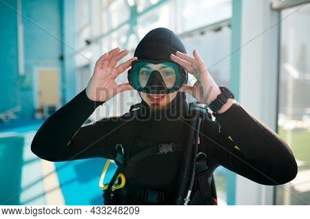 Female diver in scuba suit sitting at the poolside