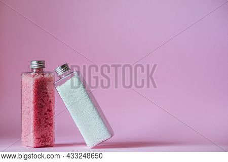 Pink Bath Shimmer And Bath Beads Stand In Transparent Bottles On A Pink Background. High Quality Pho