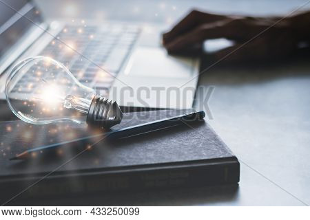 Laptop With Glowing Light Bulb And Textbook. Self Learning Or Education Knowledge And Business Study