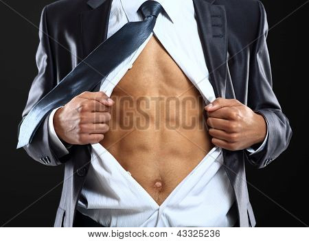Business man tears open his shirt in a super hero fashion getting ready to save the day