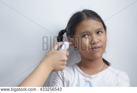 Asian Dark-skinned Girl Smiling Awkwardly While Doctor Measuring Her Body Temperature With Digital E