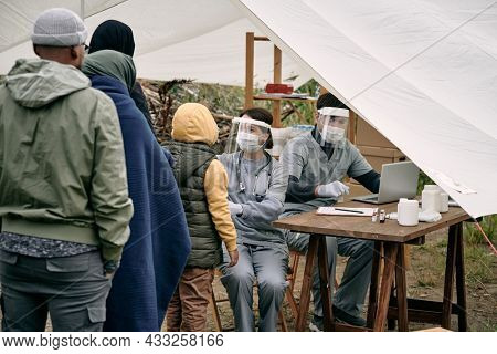 Medical specialists in protective masks sitting at table in tent and checking health of migrants standing in line