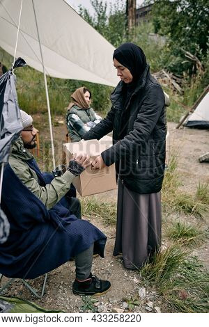 Muslim woman in black headscarf and big-size jacket sharing stuffs with young refugee in migrant camp