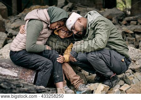 Despondent Arabian family sitting on ruins of house and hugging each other after hostilities, war concept