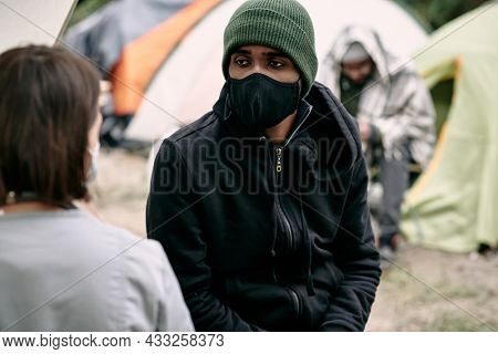 Sick young Black refugee man in facial mask and hat talking to nurse in migrant camp