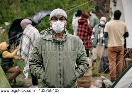 Portrait of middle-eastern man in facial mask holding hands in jackets pockets and standing against crowd of migrants
