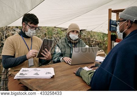 Social workers in masks sitting at table and using devices while talking to black migrant under tent