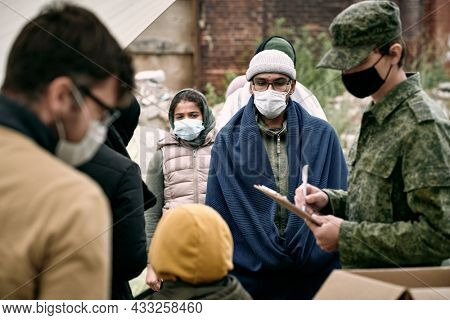 Group of middle-eastern migrants in masks standing in line for food and medicine while soldier making notes