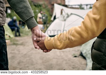 Rear view of unrecognizable children of different ages holding hands while coming in to migrant camp