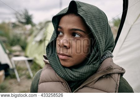 Sad Black refugee girl with covered head looking up hopefully, tent camp for migrant behind her