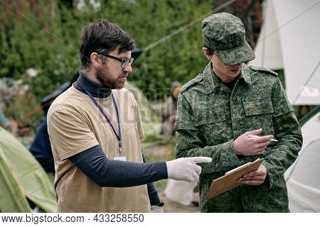 Soldier in camouflage wear holding clipboard and pointing aside while discussing food supply with social worker in migrant camp