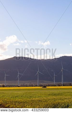 General view of wind turbines in countryside landscape with cloudy sky. environment, sustainability, ecology, renewable energy, global warming and climate change awareness.