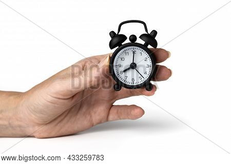 A Mini Alarm Clock In A Woman Hand Isolated On White.. 8 O'clock