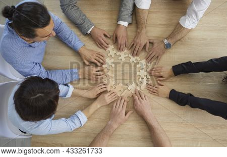 Diverse Business People Team Group Join Puzzle Pieces Sit At Desk View From Top