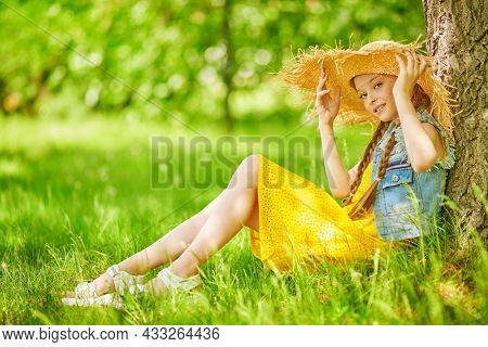 Full length portrait of a beautiful girl in straw hat having a rest in a summer park. Happy summer holidays. Summer kid's fashion.