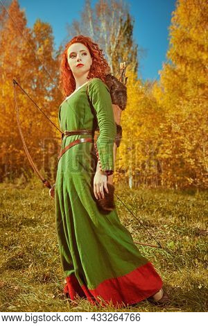 A beautiful red-haired girl archer of the Middle Ages stands against the backdrop of a bright golden autumn forest. Celtic culture. Fantasy world.