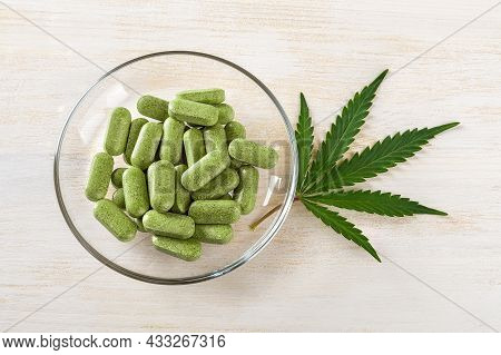 Prescription Cbd Pills Of Cannabis Sativa Weed On A Glass Saucer And Fresh Green Marijuana Leaf Over