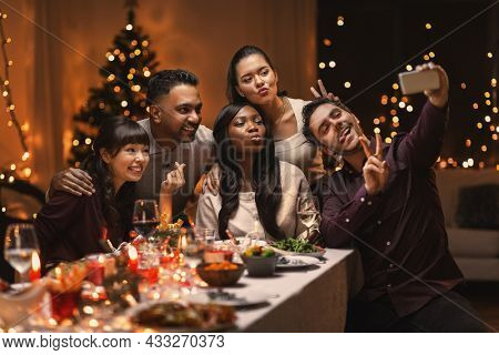holidays, party and celebration concept - multiethnic group of happy friends having christmas dinner at home and taking selfie with smartphone