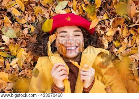 High angle view of young woman lying over yellow leaves. Beautiful woman laughing and throwing leaves while lying on ground. Top view of cheerful girl surrounded by autumn leaves at park.