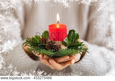 Close up of young woman hands holding Christmas candle with festive decor. Girl hands holding red burning candle with holly and branches of fir. Hands of woman burning advent light with xmas decoratio