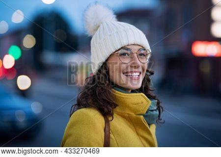 Smiling young woman wearing warm hat with eyeglasses on city street. Happy girl wearing yellow coat and standing outdoors on winter evening at bus stop. Carefree happy girl in urban center during dusk