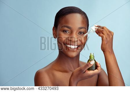 Beautiful woman applying hyaluronic acid for facial skincare and treatment with collagen moisturizer. Black beauty woman holding glass dropper and bottle isolated against blue wall with copy space.